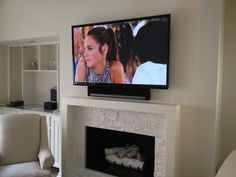 """60"""" Display and Sonos PLAYBAR mounted above a fireplace."""
