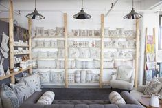 Neutral and graphic pillows organized on wood shelves // Coral & Tusk Studio Tour
