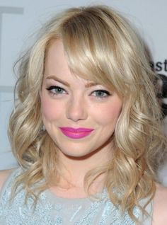 Emma Stone with light ash blonde hair, shoulder-length, curly, and wearing bangs.