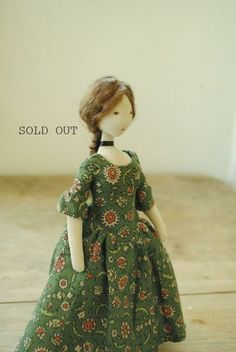 A small cloth art doll designed and handmade in Australia by Margeaux Davis from Willowynn.This is a one of a kinddoll handmadefrom carefully salvaged second handand vintagefabric.  Made from creamcotton remnants,this dollwears along, Georgian-style,green-patternedcotton dress, andagreen texturedhoodedcloak -to rug up against the cold. She also has little dark brown lace-up boots (painted on).