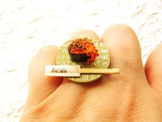 """This is part of a new series I'm making. If you look carefully you will see that the base has the word """"eat"""" written on it many times and in different sizes. This ring has a piece of tobiko (roe from flying fish-very popular in Japan) sushi and a pair of chopsticks. Eat! Go ahead and enjoy!      It is on a silver tone adjustable band that will fit most ring sizes. It measures about 2.5 cm wide."""