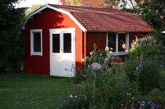 Inmitten eines idyllischen Gartens steht dieses schwedenrote Gartenhaus, das Gemütlichkeit und Charme ausstrahlt.