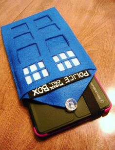 No-Sew T.A.R.D.I.S. Case for Handheld Devices | 3 Dark Blue Sheets of Felt; 1 White Sheet of Felt; 1 Black Sheet of Felt; 1 Clear Button/Jewel; White Fabric Paint; Sharpie; Fabric Glue; Scissors.