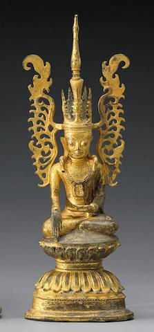A Burmese gilt bronze figure of the Buddha Shan State, 18th Century Portrayed in his regal Jambupati manifestation with an elaborate crown framing his serene visage, the lithe figure exhibiting the bhumisparsa mudra while seated in a pose of meditation on a tall double-lotus pedestal on a triangular plinth. 15 1/4in (39cm) high