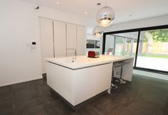 White satin lacquer kitchen design with kitchen island.  Kitchen style is handleless, with a white Corian worktop.