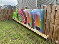 Build bottom box out of fence pickets. Attach to fence Screw in eye hooks midway up fence to attach bungee cords to keep floats in place. Easy removal and storage. Above Ground Pool Landscaping, Above Ground Pool Decks, Backyard Pool Landscaping, In Ground Pools, Pool Toy Storage, Pool Float Storage, Outdoor Storage, Float Pool, Pool Organization