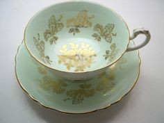 Mint green tea cup and saucer made by Paragon England  Beautiful gold roses on the center of both pieces and gold filigree.  The backstamp date this