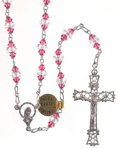 """Swarovski Crystal """"Madonna in the Stars"""" Sterling Rosary. High quality Swarovski crystal beads. Imported from Italy. Pink & clear Swarovski rosary beads on solid sterling silver links. Each bead comprises of two Pink and one Clear Swarovski crystal. The beautifully ornate crucifix is 1-3/4"""" in length and made of sterling silver. Features a lovely sterling """"Madonna in the Stars"""" centerpiece. Elegantly box. This strikingly unique rosary has an inner length of approx. 36"""", so it may also be…"""