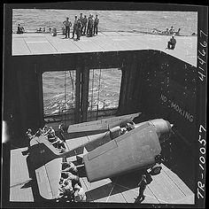 Navy crewmen aboard USS Monterey (CVL-26) bringing an F6F Hellcat to the flight deck on elevator, June 1944.