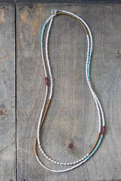 This delicate long beaded necklace is made up of seed beads in bronze and palest dove grey, with turquoise, garnet and clear crystal quartz gemstone accents. This piece works as a long necklace, or doubled, or wrapped around the wrist or ankle. Finished with a sterling silver spring clasp and findings.  This necklace is delicate, with tiny seed beads, and the gemstones measure approx 2-3mm. Necklace measures 35 inches total, but I am happy to make to any specification. Please just leave a…