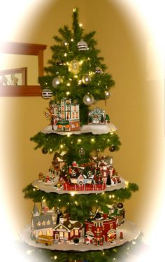 'The Original Snow Village' (Dept 56) displayed throughout  a Christmas tree. Good idea for a foyer, hallway, etc. http://www.department56.com/content.aspx?cid=VLSV&ms=PRD&msi=59005&smenu=products