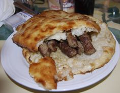Cevapi : a grilled dish of minced meat, a type of kebab, found traditionally in the countries of southeastern Europe. They are considered a national dish in Bosnia . They are usually served of 5-10 pieces on a plate or in a flatbread (lepinje or somun), often with chopped onions, sour cream, kajmak, ajvar, cottage cheese, minced red pepper and salt.. TRY IT :)