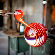 In this picture a person is spinning red colored glass onto a clear orb of glass. The amount of patience and dexterity it takes to do this boggles my mind.