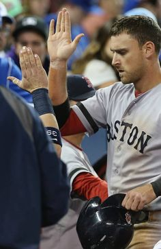 TORONTO, CANADA - AUGUST 13: Will Middlebrooks #16 of the Boston Red Sox is congratulated by teammates in the dugout after scoring a run in the seventh inning during MLB game action against the Toronto Blue Jays on August 13, 2013 at Rogers Centre in Toronto, Ontario, Canada. (Photo by Tom Szczerbowski/Getty Images)