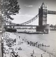 Londoners enjoying sunshine and low tide at the Tower beach. This had opened two years previously with sand imported by lighters. Some Thames watermen with their skiffs have attracted keen interest on the water's edge. blog.museumoflondon.org.uk