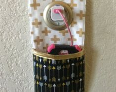 Protect your iPhone / ipod/ and cord with this unique cell phone charger holder. The grommet sits perfectly on the charger while the phone and cord fit snugly in the pocket.  The pouch is made from designer fabric and very stylish and unique.  Approximately: 9.5X4.5 pocket 5.5 long. Grommet opening: 1-9/16 diameter; Grommet overall: 2-3/8. Please be sure and measure your phone to ensure fit; as this cell phone charger holder will not fit all cell phone models.  ***Since ea...