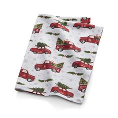 Laden with Christmas trees, cheery red vehicles hurry home, creating a holiday traffic jam on off-white cotton. Oversized and absorbent, the dishtowel softens with every washing.