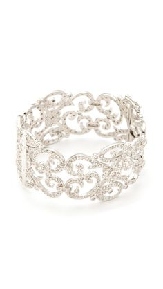 A bracelet/cuff like this: with intricate scrollwork. Feminine and elegant.