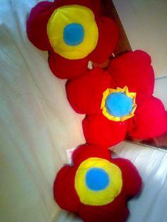 Almohadones en forma de flor. Realizados en telas de algodón de colores firmes y rellenos con vellón siliconado.