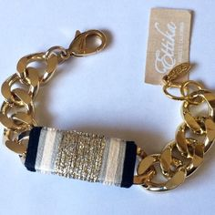 Ettika Gold ID Bracelet with Silk Thread Ettika of Los Angeles Fancy That Gold ID Bracelet in Black, Beige, Silver and Metallic Sand 7 1/2 inches. A fanciful chunky chain bracelet with mutlticolors of black, gray & gold woven over a gold ID bracelet. NWT. Ships in a black box that is perfect for gift giving. Retails on the designers site for $55. Ettika of Los Angeles Jewelry Bracelets
