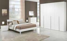 Dormitorio para pareja, equipada de una cama de matrimonio un grande armario, un escaparate, dos mesillas de noche con lamparas y un alfombra. Los colores de la habitación son blanco, marrón, beije, y gris oscuro.