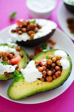 Spicy roasted chickpeas, creamy avocado, and tangy garlic yogurt sauce make these flavorful nutrition powerhouse stuffed avocados!