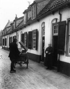 Afbeelding van broodbezorger B.J. Nijenhuis met zijn broodkar bij de Bruntskameren aan het Lepelenburg te Utrecht, met rechts bij de deuropening mej. M.E. van Doorn (Lepelenburg 14) en en links van haar mej. Pauw.  N.B. Het adres van de Bruntskameren is in 1981 gewijzigd in Bruntenhof. 1937