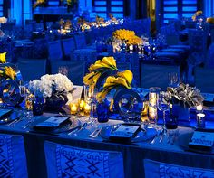 Pinspots illuminate gorgeous floral centerpieces while the rest of the venue is set in a blue wash.