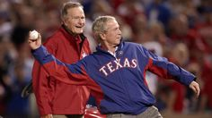 Former US presidents George W Bush (front) and his father George HW Bush, pitch before a Texas Rangers game in 2010