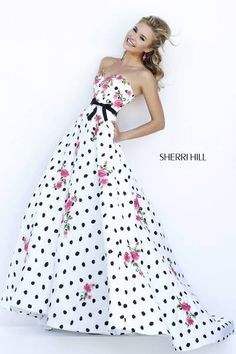Sherri Hill #32202 All over polka dots are punctuated with floral bouquets on the fabric of this classic strapless ball gown. Satin bow at the waist breaks up the full skirt from the sweetheart neckline.