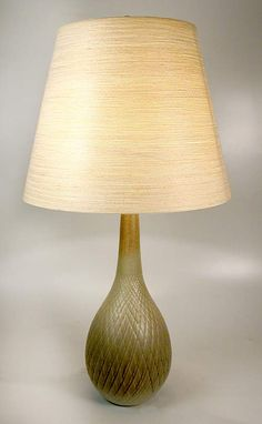 This beautiful mid-century modern pottery lamp was made in Canada in the 1950's by the Bostlands. Lotte and Gunnar Bostland emigrated from Denmark to Canada and produced these iconic mid-century modern lamps. The lamp is incised with a quilted diamond pattern and glazed in sage green with highlights of iridescent turquoise. Hard shell  fiberglass and linen strand shade. Image © Eclectisaurus. Visit our shop at 249 Gerrard St E, Toronto. 416-934-9009 www.eclectisaurus.com
