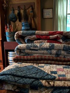 This could be Elsa Brantenberg's kitchen table full of quilts on a Thursday after the quilting circle met at her farm in THE QUILTED HEART novellas. www.monahodgson.com