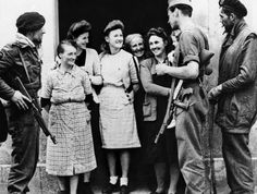 Villagers of Amfreville, France, chat with members of a French commando unit who landed in Normandy with Allied forces on June 20, 1944. (AP Photo)