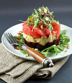stacked beet, avocado, and grapefruit salad (with arugula, pinenuts and sprouts to garnish)
