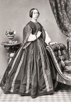 Pagoda sleeves, ornate trim on bodice and dress. Interesting hair, is it a braid over her ears?