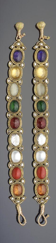 A pair of Indian gem-set enamelled gold Navratna Bracelets   each comprising nine interlinking oval elements set in gold, verso with floral enamel decoration   each 18.5 cm. long