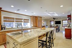 12415 BROKEN BOUGH. Alternate view of the kitchen  open to the breakfast room featuring Jura Stone floor, expansive island with an abundance of beautiful wood cabinetry for storage, space for seating, sink & induction burner! Features large windows w/ shades. Bernstein Realty, Houston Real Estate.