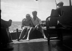 """EH01539N Ernest Hemingway with his arm around his son, Jack """"Bumby"""", aboard his boat, Pilar, circa 1930s."""