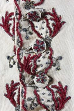 Detail embroidery, waistcoat, c. 1760. Ivory silk faille embroidered in wine Chenille and silver thread in chain stitch.