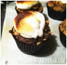 S'mores cupcake. Dark chocolate cupcake with crumbled graham crackers baked on top, topped with a big marshmallow and then put under the broiler.    Cupcake Rehab - cupcakerehab.com: Beating batter & people with whisks since 2007!