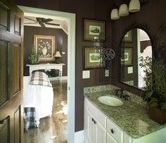 These homeowners went with a dark brown to match the color of the bedroom. For the bathroom, they added leaf pulls to the mirror, an oil-rubbed bronze faucet, granite counters and small oil paintings. #smallbath #bathrooms