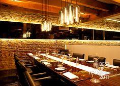 Espelho bronze retroiluminado, parede pedra, luminárias garrafa, cadeiras couro preto, mesa madeira com trilho branco