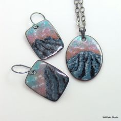 Alpenglow and a sense of the vertical describes my mountainscape impression. Looking from a birds eye view, the mountain landscape themed enameled dangle earrings and pendant are original and one of a kind. Kiln-fired copper enamel earrings & the similar pendant feature handmade oxidized sterling ear wires and a sterling pendant bail. Each petite copper rectangle is about 1 tall and the dangle earrings are about 1 1/2 long measured from the top of the ear wire. The larger oval pendan...