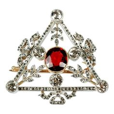 FABERGE Triangular Brooch. A Russian 56 standard gold, diamond and spinel brooch attributed to Faberge (maker's mark partially overstruck by the assay mark)