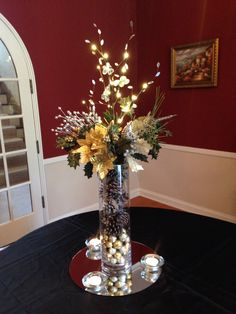 Christmas themed centerpiece used to decorate entrance at a fund raiser.  Lighted branches, gold and silver picks, tall vase with pine cones.  The small glitter balls were used to cover the battery case.