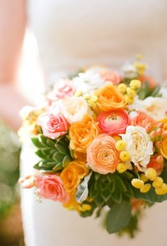 Bouquet of roses and ranunculus in peach, orange, pink, and, white, paired with green succulents.