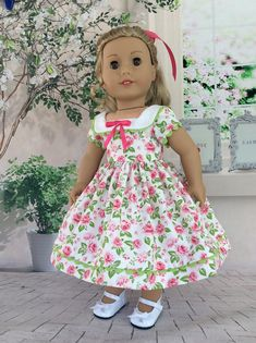 Tennys dress is made of a beautiful pink rose print, a premium cotton fabric. It has a square neck and collar, The collar has green rickrack around the edge and a ribbon on the center front. The sleeves have rickrack around the bottom as does the grow hem. The back closes with Velcro and