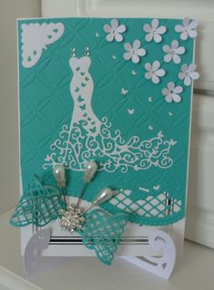 Tattered lace dress die. Inspiration for the bow from a tattered lace die of which I used a Marianne die,the card stand & flowers were from a file  I down loaded to cut on my silhouette