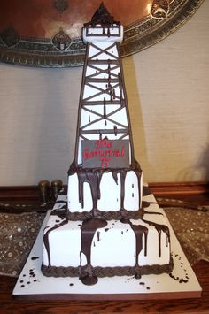 """Oil Derrick Cake - The bottom tier is a 12"""" square cake and above is a 6"""" square cake. The oil derrick is made of rice crispies, covered with fondant. The oil drips are chocolate melts."""