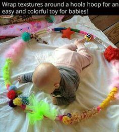 Het is een hoepel waar je je kind kan inleggen, het stimuleert de zintuigen en het stimuleert het kind ook om zen hoofd recht te houden. Aan de hoepel zelf moet je kleurrijk materiaal hangen en ook materiaal dat geluid maakt, het kind gaat er boeiend naar kijken en het ook willen aanraken.